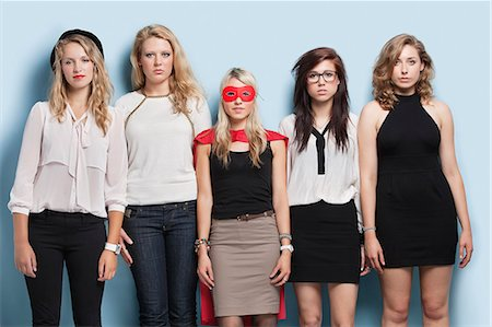 superhero costume - Portrait of five young women standing side by side against light blue background Stock Photo - Premium Royalty-Free, Code: 693-06379995