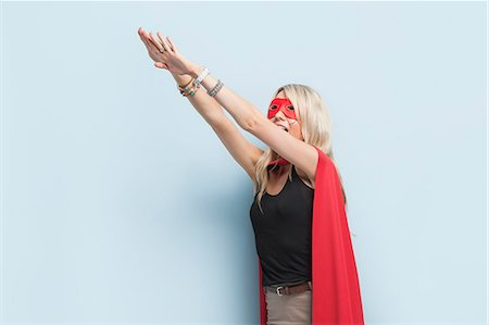 superhero costume - Young woman in superhero outfit pretending to leap in the air against light blue background Stock Photo - Premium Royalty-Free, Code: 693-06379993