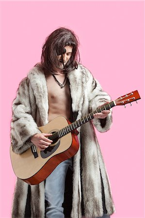 Young man in fur coat playing guitar against pink background Stock Photo - Premium Royalty-Free, Code: 693-06380011