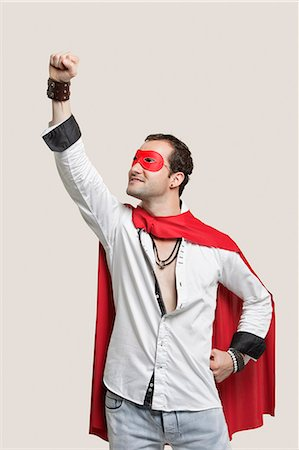 Young man in superhero costume standing against gray background Stock Photo - Premium Royalty-Free, Code: 693-06380036