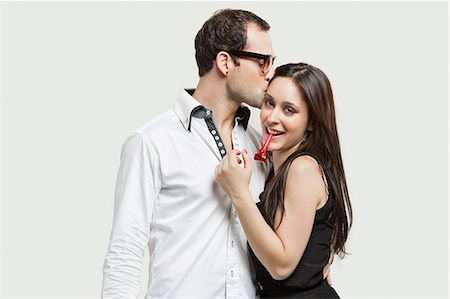 Young couple with party puffer against gray background Stock Photo - Premium Royalty-Free, Code: 693-06380033