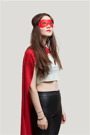 superhero costume - Young woman in superhero costume looking up against gray background Stock Photo - Premium Royalty-Free, Code: 693-06380044