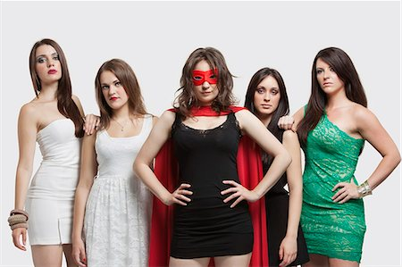 superhero costume - Young woman in superhero costume standing together with friends over gray background Stock Photo - Premium Royalty-Free, Code: 693-06380048