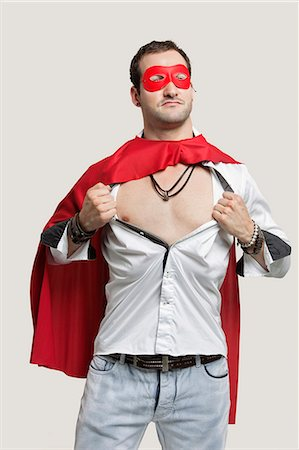 Young man in superhero costume standing against gray background Stock Photo - Premium Royalty-Free, Code: 693-06380041