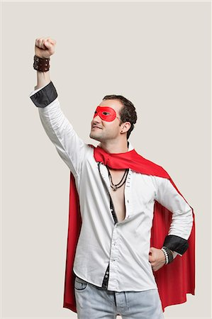 superhero costume - Young man in superhero costume with hand raised against gray background Stock Photo - Premium Royalty-Free, Code: 693-06380043