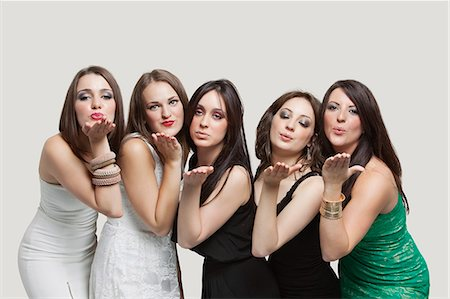 Five young women blowing kisses over gray background Stock Photo - Premium Royalty-Free, Code: 693-06380052