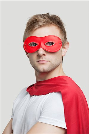 Portrait of young man wearing superhero costume against gray background Stock Photo - Premium Royalty-Free, Code: 693-06380064