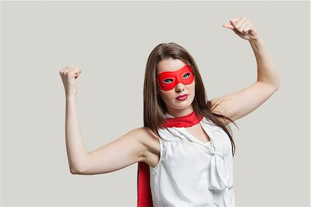 superhero costume - Portrait of a young woman in super hero costume flexing muscles over gray background Stock Photo - Premium Royalty-Free, Code: 693-06380078