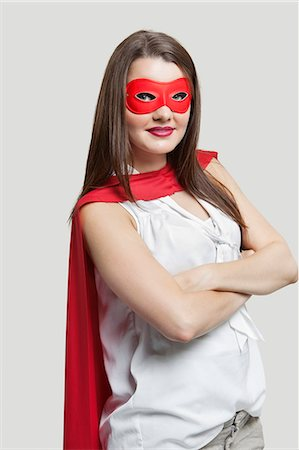 Portrait of a young woman in super hero costume over gray background Stock Photo - Premium Royalty-Free, Code: 693-06380079