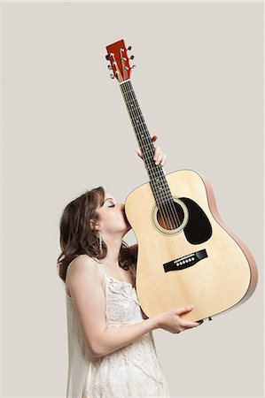 Young woman kissing guitar against gray background Stock Photo - Premium Royalty-Free, Code: 693-06380071