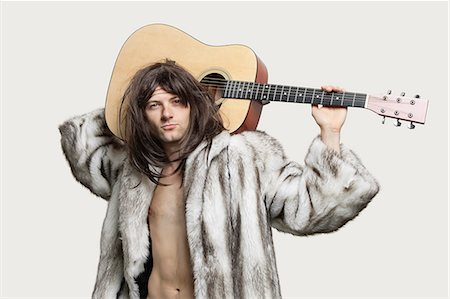 fur - Portrait of young trendy man with guitar over gray background Stock Photo - Premium Royalty-Free, Code: 693-06380085
