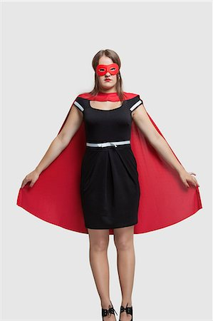 superhero costume - Young woman standing in superhero costume over gray background Stock Photo - Premium Royalty-Free, Code: 693-06380083