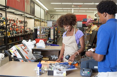 Portrait of an African American female store clerk standing at checkout counter scanning item serving male customer Stock Photo - Premium Royalty-Free, Code: 693-06403175