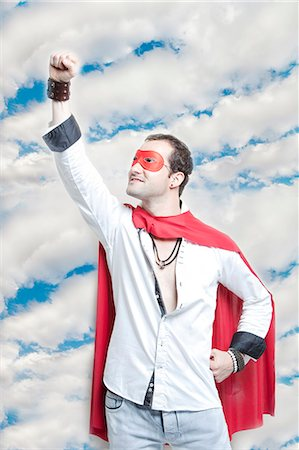 superhero costume - Young man in superhero costume with hand raised against cloudy sky Stock Photo - Premium Royalty-Free, Code: 693-06403199