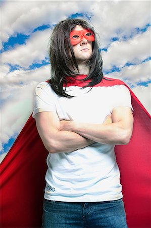 Young man in super hero costume with arms crossed against cloudy sky Stock Photo - Premium Royalty-Free, Code: 693-06403206