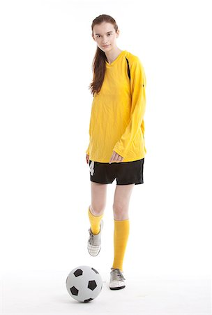 Portrait of young female soccer player kicking the ball against white background Stock Photo - Premium Royalty-Free, Code: 693-06403248
