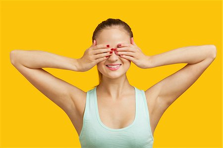 silhouette hand - Beautiful young woman covering eyes over yellow background Stock Photo - Premium Royalty-Free, Code: 693-06403271