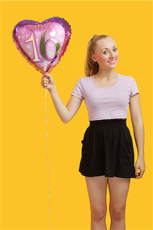 female silhouettes heart - Portrait of beautiful young woman holding heart shaped birthday balloon over yellow background Stock Photo - Premium Royalty-Free, Code: 693-06403296