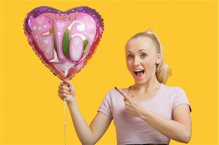 female silhouettes heart - Portrait of surprised young woman holding heart shaped birthday balloon over yellow background Stock Photo - Premium Royalty-Free, Code: 693-06403297