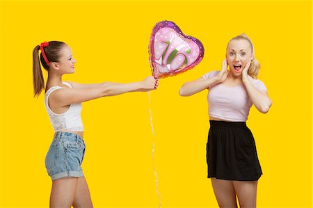 Happy young woman giving birthday balloon to amazed woman standing over yellow background Stock Photo - Premium Royalty-Free, Code: 693-06403299