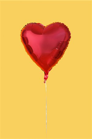 shape - Red heart shaped balloon over yellow background Stock Photo - Premium Royalty-Free, Code: 693-06403291
