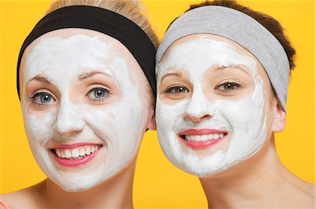 facial - Portrait of two happy women with face pack on their faces over yellow background Stock Photo - Premium Royalty-Free, Code: 693-06403309
