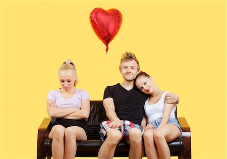 Portrait of young couple sitting on sofa with female friend feeling left out over yellow background Stock Photo - Premium Royalty-Free, Code: 693-06403302