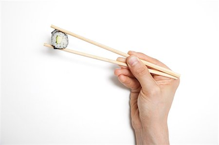 Man's hand holding sushi roll in chopsticks against white background Stock Photo - Premium Royalty-Free, Code: 693-06403364