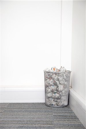 Wastebasket full of crumpled paper in corner against white wall Stock Photo - Premium Royalty-Free, Code: 693-06403376