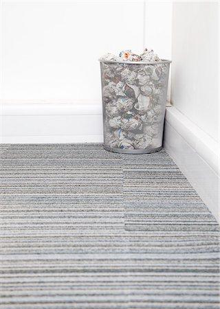 Wastebasket full of crumpled paper in corner on carpet floor in room Stock Photo - Premium Royalty-Free, Code: 693-06403377