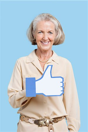 Portrait of senior woman in casuals holding fake like button against blue background Stock Photo - Premium Royalty-Free, Code: 693-06403415