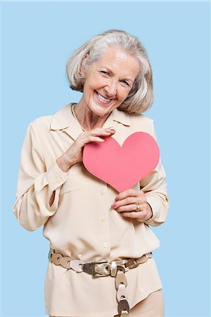 female silhouettes heart - Portrait of senior woman holding red paper heart against blue background Stock Photo - Premium Royalty-Free, Code: 693-06403424