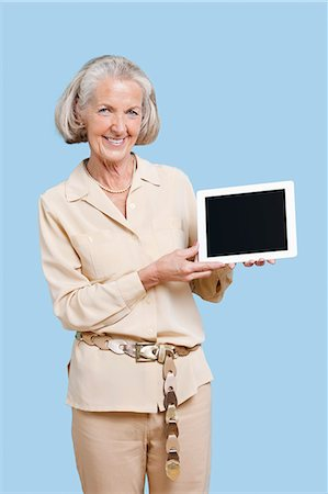 showing - Portrait of senior woman showing tablet PC against blue background Stock Photo - Premium Royalty-Free, Code: 693-06403433