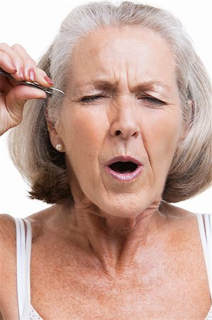 Senior woman tweezing eyebrows against white background Stock Photo - Premium Royalty-Free, Code: 693-06403451