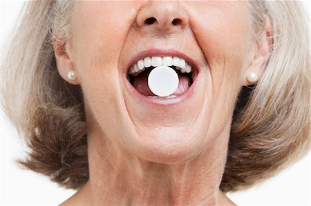 Senior woman with a pill between her teeth against white background Stock Photo - Premium Royalty-Free, Code: 693-06403463