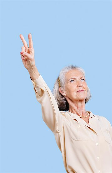 Senior woman in casuals gesturing peace sign against blue background Stock Photo - Premium Royalty-Free, Image code: 693-06403479