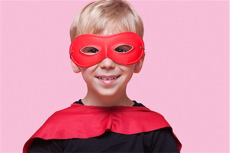 superhero costume - Portrait of a happy boy in superhero costume over pink background Stock Photo - Premium Royalty-Free, Code: 693-06403547