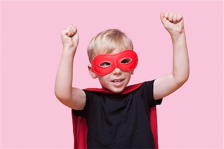 Young boy dressed in superhero costume with arms raised over pink background Stock Photo - Premium Royalty-Free, Code: 693-06403548