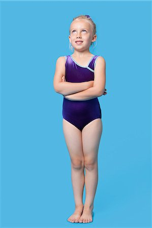 Young female gymnast with arms crossed looking up over blue background Stock Photo - Premium Royalty-Free, Code: 693-06403557