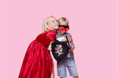 dress up girl - Happy young girl in princess costume hugging boy pretending to be her hero over pink background Stock Photo - Premium Royalty-Free, Code: 693-06403553