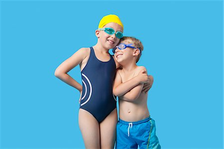 Happy young siblings in swimwear with arm around over blue background Stock Photo - Premium Royalty-Free, Code: 693-06403574