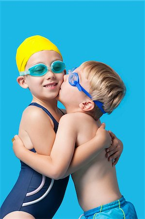 Young siblings in swimwear embracing and kissing over blue background Stock Photo - Premium Royalty-Free, Code: 693-06403572