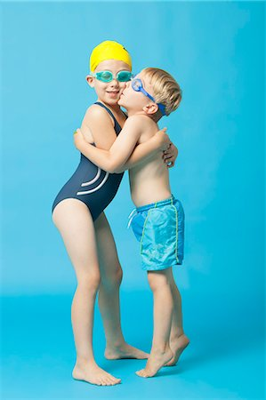 Young siblings in swimwear embracing and kissing over blue background Stock Photo - Premium Royalty-Free, Code: 693-06403573