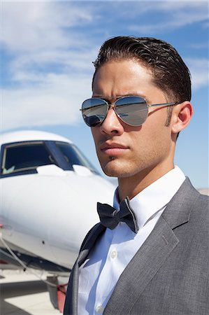 rich lifestyle - Handsome young men wearing sunglasses with private plane in background Stock Photo - Premium Royalty-Free, Code: 693-06435748