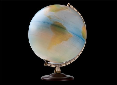 Close-up of spinning globe over black background Stock Photo - Premium Royalty-Free, Code: 693-06435803