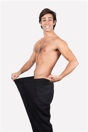slim - Portrait of happy young man wearing oversized pants against gray background Stock Photo - Premium Royalty-Free, Code: 693-06435877
