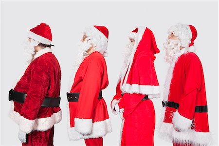 People in Santa costume standing in row against gray background Stock Photo - Premium Royalty-Free, Code: 693-06435898