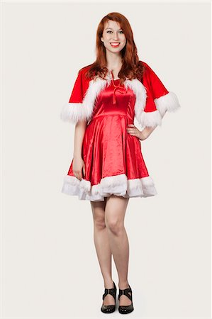 pretty - Portrait of happy young woman in Santa costume standing against gray background Stock Photo - Premium Royalty-Free, Code: 693-06435891