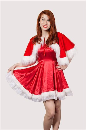 pretty - Happy young woman in Santa costume standing against gray background Stock Photo - Premium Royalty-Free, Code: 693-06435892