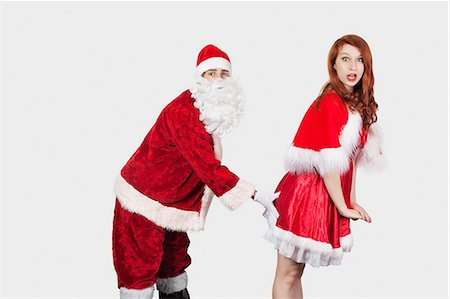 desire - Portrait of Santa touching Mrs. Santa inappropriately against gray background Stock Photo - Premium Royalty-Free, Code: 693-06435893